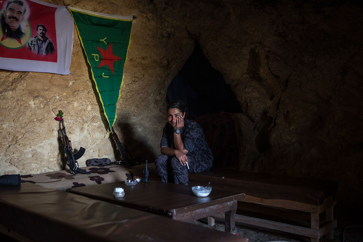 A YPJ fighter sits in a frontline position west of the Euphrates River. [Mauricio Morales/Al Jazeera]