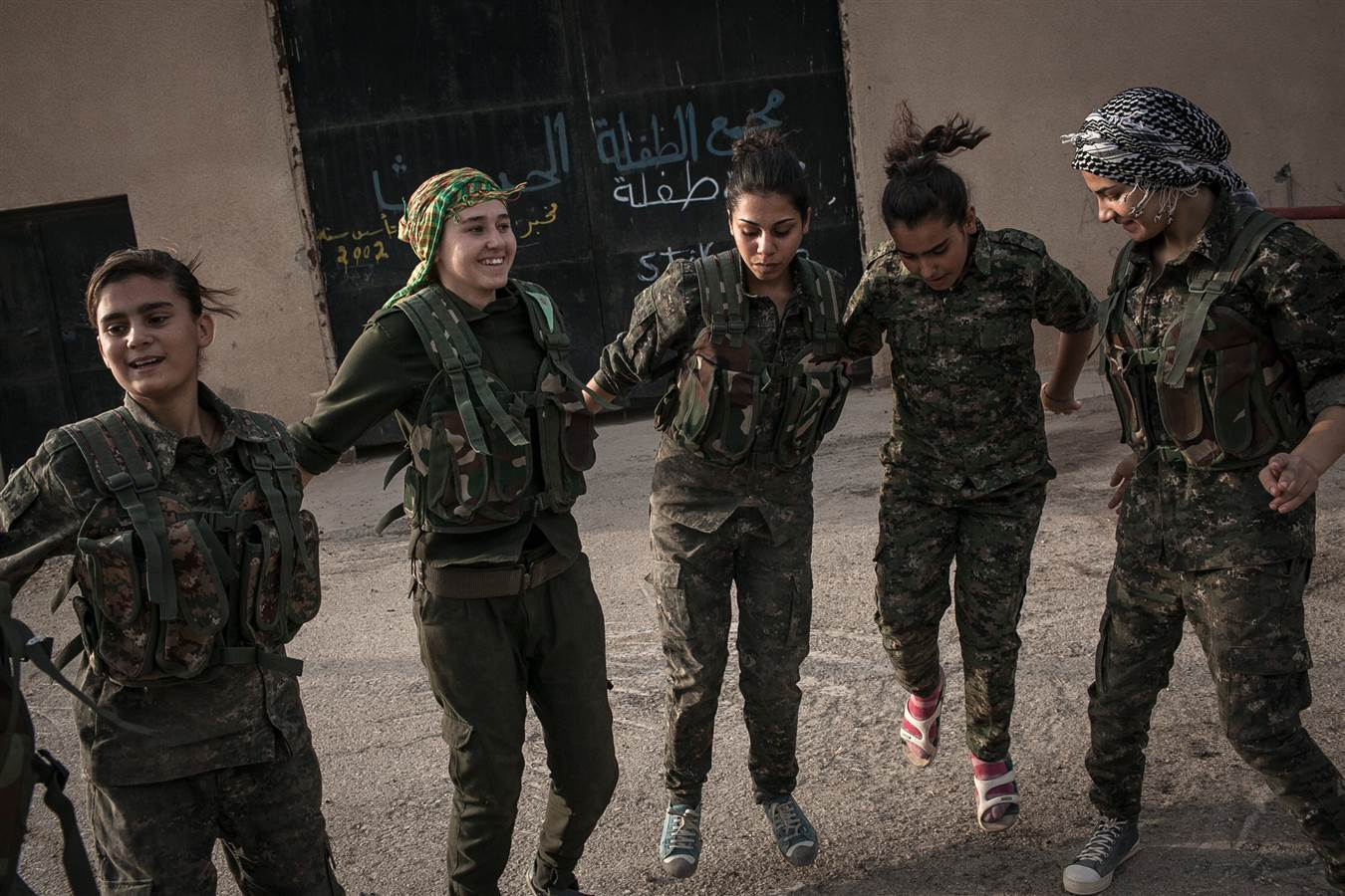 Young recruits take a break by dancing and singing traditional YPJ songs at dawn, near Derek City, Syria. Credit: Erin Trieb